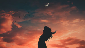 Woman standing in front of sunset with crescent moon in the sky