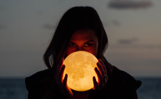 Woman holding moon lamp in front of her face