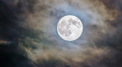 full moon in partially clouded sky