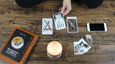 tarot spread with 3 cards and a candle & phone on the ground. Person holding card