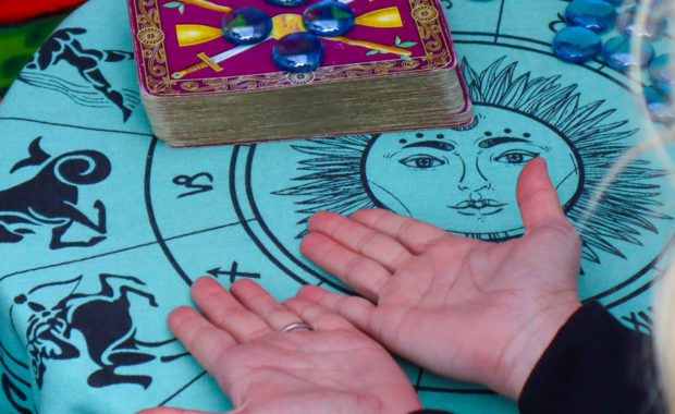 blond lady with both hands on table with palm up. The table cloth slight blue with the sun in the middle and the zodiac symbols around it. Tarot cards are also on the table.