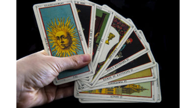hand holding tarot cards in a fan spread with ton card showing a sun
