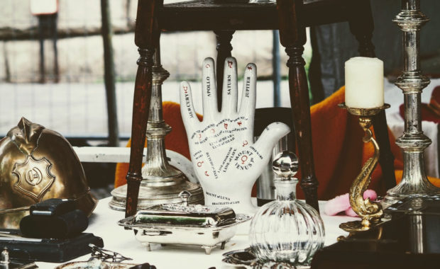 picture of palmistry hand on table surrounded by objects