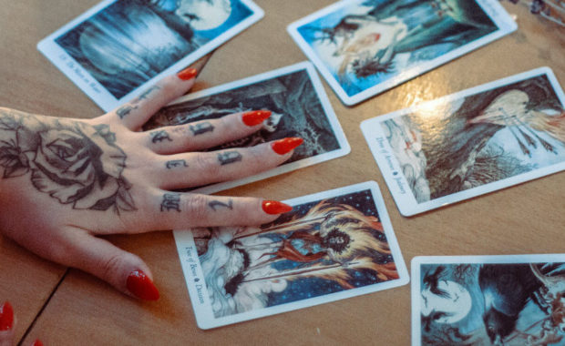 girl with red nails and tattoos on her hand holding a 6-card tarot spread on the table