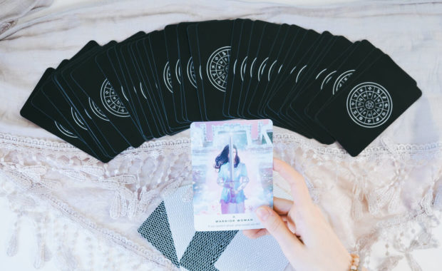 a picture of a woman's hand holding a colorful tarot card up above a background of black tarot cards on a table