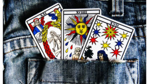 3 colorful tarot cards in a jean pocket showing a person, sun, and stars