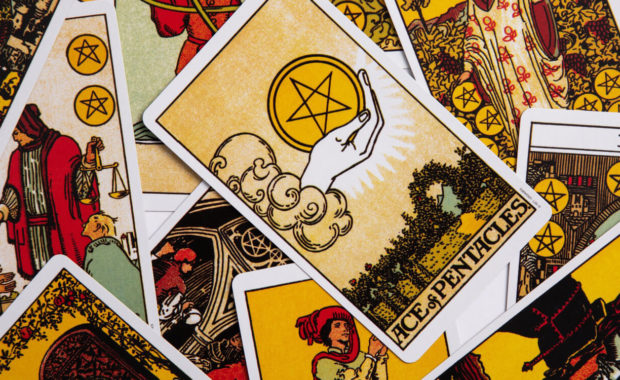 A messy pile of yellow, black and red taro cards with the ace of pentacles as the focus card