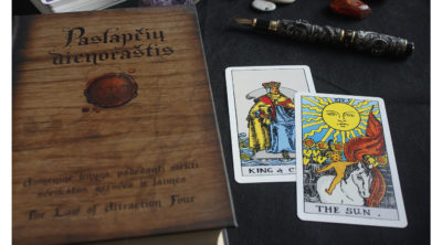 the sun tarot card sitting on a table with another card and a book titled the law of attraction four