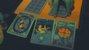 picture showing 3 tarot cards on table with hand placed on card stack