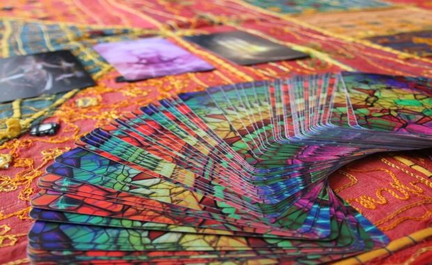 colorful rainbow colored card deck spread out on an orange and yellow table cloth
