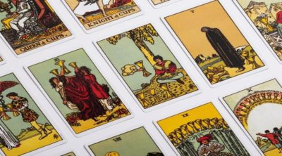 picture of yellow, green and red rider waite tarot cards lined up on a white table