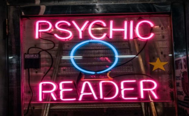 glowing sign that reads psychic reader in pink and blue with a circle in the middle