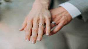 image of a married couple with the woman hand over the mails with wedding rings on