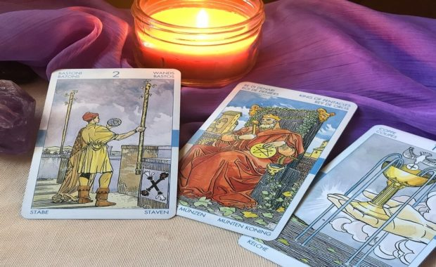 2 of wands, king of pentacles, and 1 of chalice cards all sitting on a purple cloth with an amethyst next to it and a yellow candle burning in the background