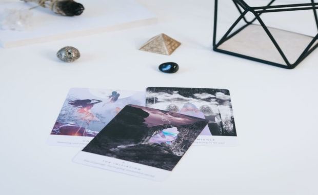 3 tarot cards laying on a white table with crystals around it and a black sphere
