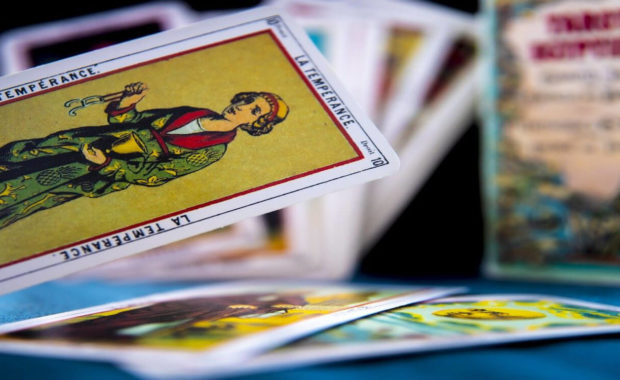 image of white, red, and white temperance card in the foreground with blurred tarot card pile in the background