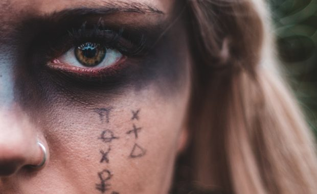 Woman with astrology symbols painted on face