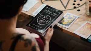 Woman reading the Witch Bible with Tarot Cards