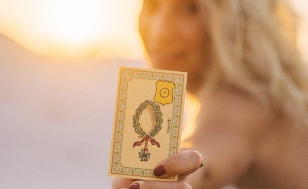 woman holding a single tarot card