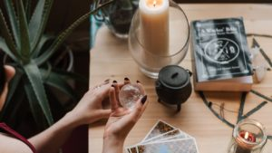 Woman holding crystal ball with Tarot cards