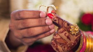 two hands holding wedding rings