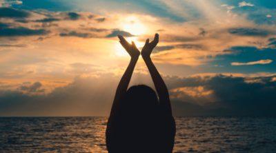 Woman raising hands at sunset